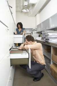 ThinkstockPhotos 200331909 001 200x300 - Businessman and businesswoman looking through filing cabinets